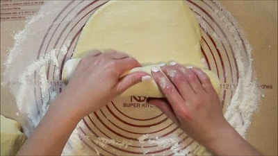 Rolling dough up and shaping into a bread loaf.