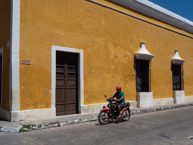 Hombre en moto pasando frente a fachada amarilla en Izamal