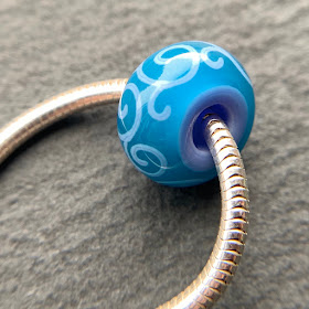 Handmade lampwork glass big hole bead by Laura Sparling made with CiM Peacock Feather
