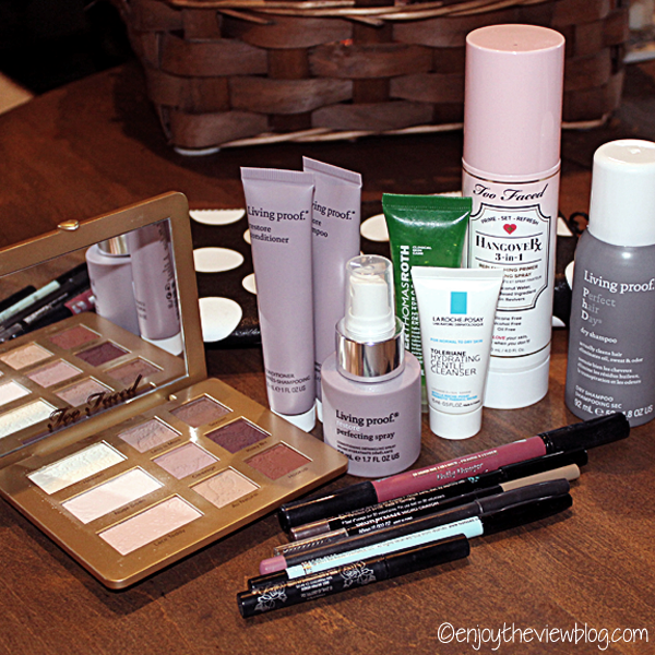 various beauty products (some travel-size) sitting on a wooden table