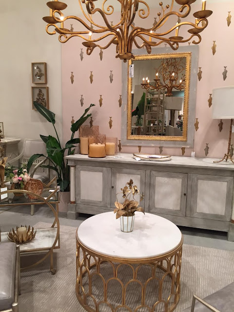 Gray and white sideboard in room with gold table and mirror