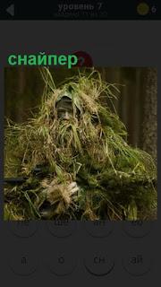 снайпер спрятался в камуфляже и в траве с винтовкой