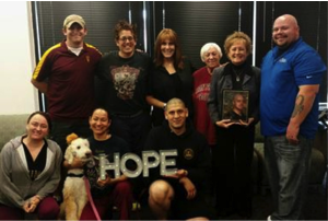 "Group picture of people holding a ""HOPE"" sign."