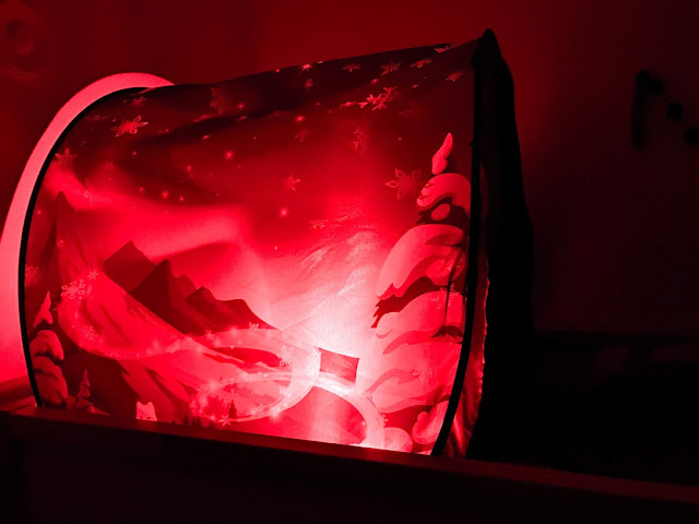 A side view of the Wonderland Dream Tent in the dark with a red light shining inside