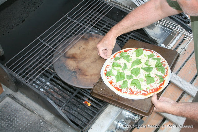 A pizza is being transferred to a preheated pizza stone on the grill.