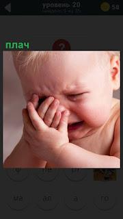 Маленький ребенок плачет, руками закрывая свое лицо