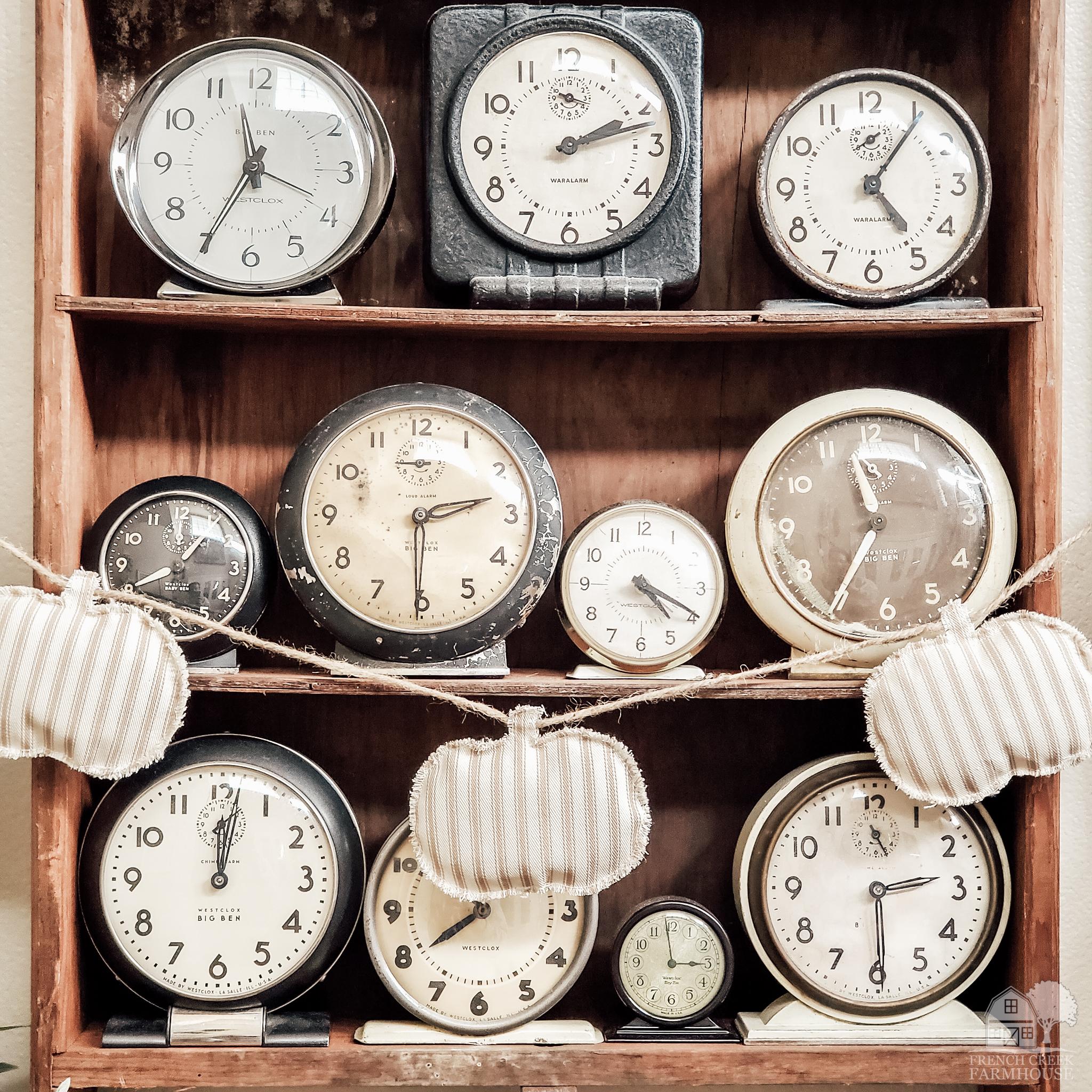 Pumpkin garland hanging in front of vintage clocks