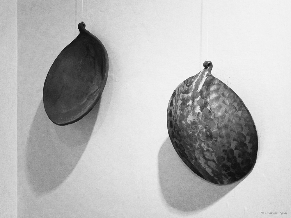 A Black and white Minimalist Photo of two Earthen clay art hanging on a wall by a thread.