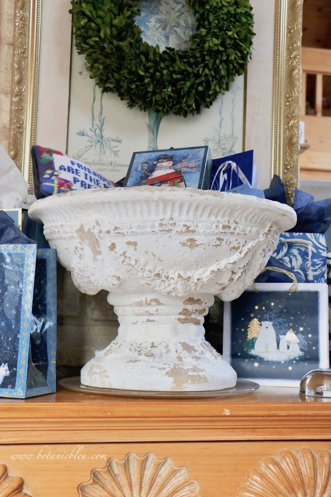 French country blue Christmas presents are displayed in a French country white pedestal urn