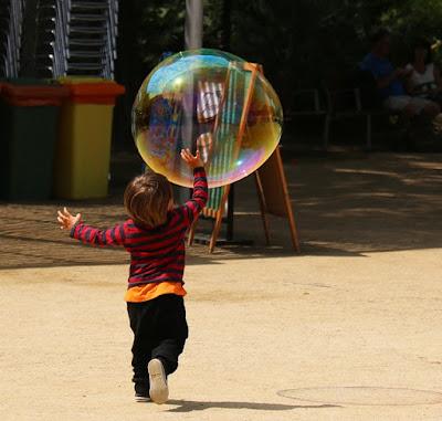Kind spielt mit riesiger Seifenblase