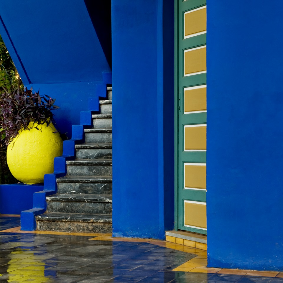 paredes azules, verdes y ocre con macetas amarillas