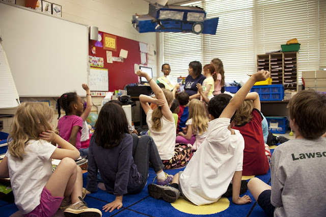 A number of children sat on the floor around a teacher, some of the children have their hands up