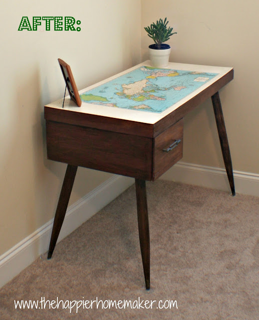 A map top wood desk with a picture and small plant