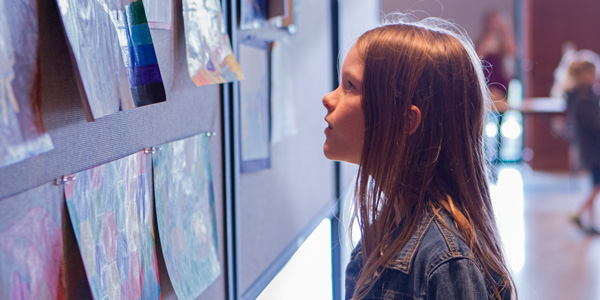 Young girl admires the artwork on display in Montezuma Hall