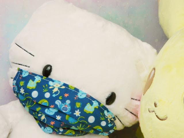 A hello kitty plush toy wearing a water type pokemon mask