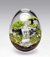 Teraryum, içinde ağaçlar bitkiler şelale ve sevimli bir ev bulunan yumurta şeklinde cam fanus teraryum