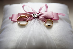 two gold wedding rings on a cushion