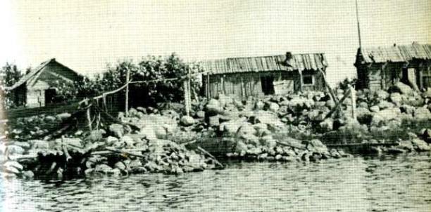 Vanha kuva kalastusmajoista kivisellä rannalla.