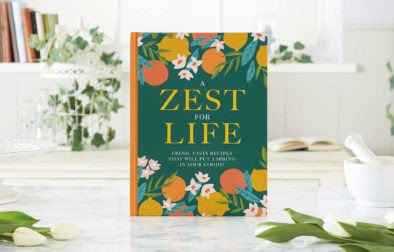 A Zest For Life Cookbook depicted on a white countertop with a miscellany of plants and other items surrounding.