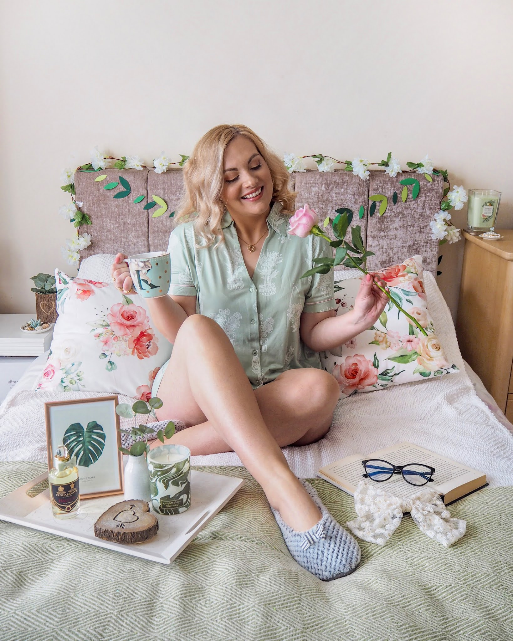 Spring Photography Props & Home Decor, Girl sitting on a bed in sage green pyjamas holding a rose and a mug of tea there are lots of floral spring props like cushions and flower garlands around her.