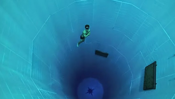 A diver free falling into the depth of Nemo 33.