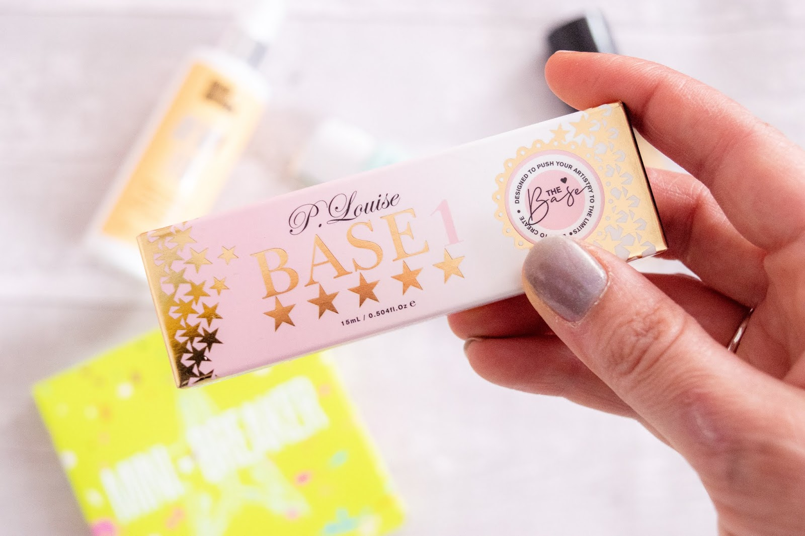 A close up of the P.Louise Base Primer box. The box is pink with gold stars around the edge.