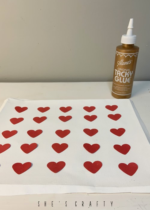 Use tacky glue to attach heart punches to reverse canvas for Valentine's Art