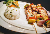Hawaiian Chicken kebabs kabobs is serving with parsley butter rice and grilled vegetables.