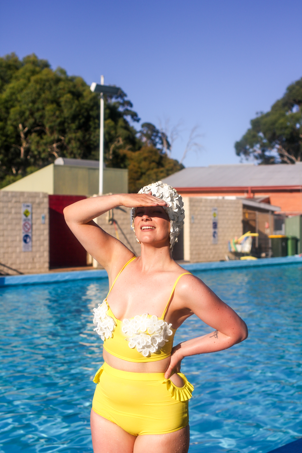 Liana of @findingfemme wears a yellow and white vintage bikini with a white floral swimming cap