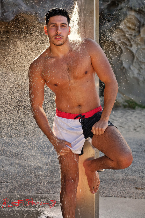 Three quarter back-lit body shot in swimming trunks with sunlight in shower spray. Male modelling portfolio shot on Location in Sydney Australia by Kent Johnson.