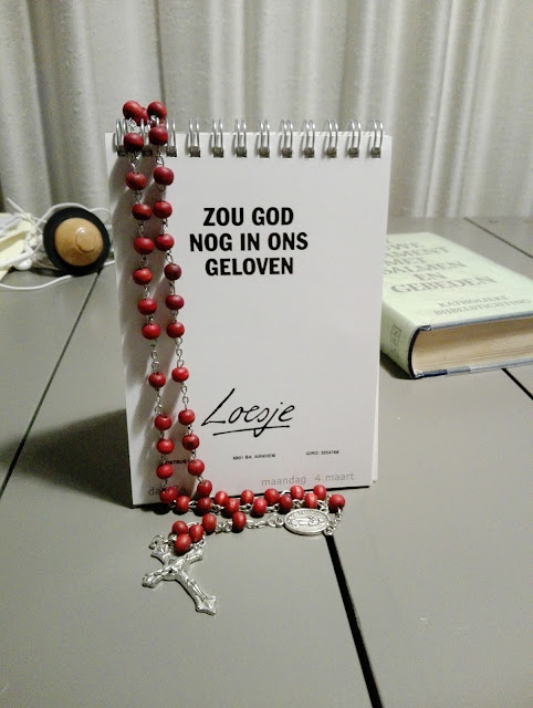 Loesje-tekst 'Zou God nog in ons geloven' op bureau met rozenkrans