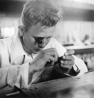 Black and white vintage photograph of a man wearing a magnifying single eye-piece, closely examining a small item in his hands. He is wearing a white lab coat.