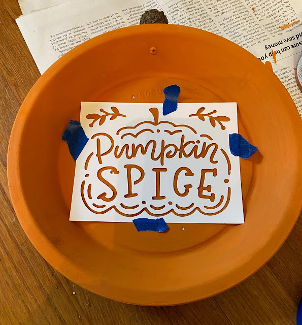 Photo of an orange pie tin with a stencil on top.