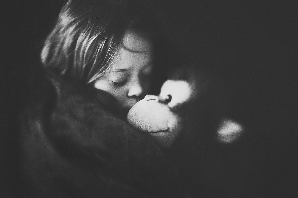 Black and white lensbaby image of a girl with her favorite cuddle toy