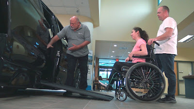 A man is pointing to a foldout ramp of a BraunAbility minivan. He is talking to a girl and her father, as they both look up the ramp and into the vehicle.