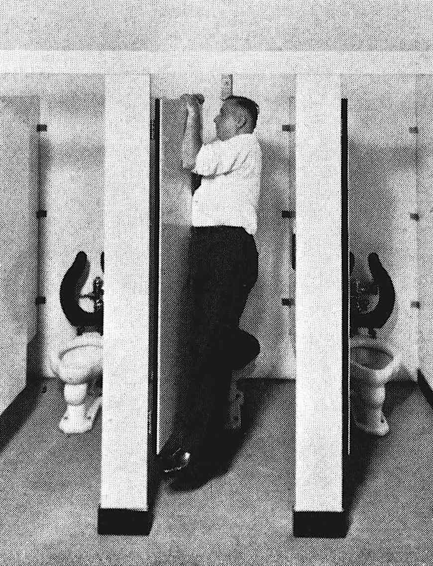 odd photograph of a man hanging from a washroom stall door to test it's strength
