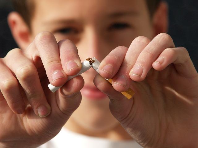 Kind bricht eine Zigarette ist gegen Drogenkonsum und sexuelle und körperliche Gewalt