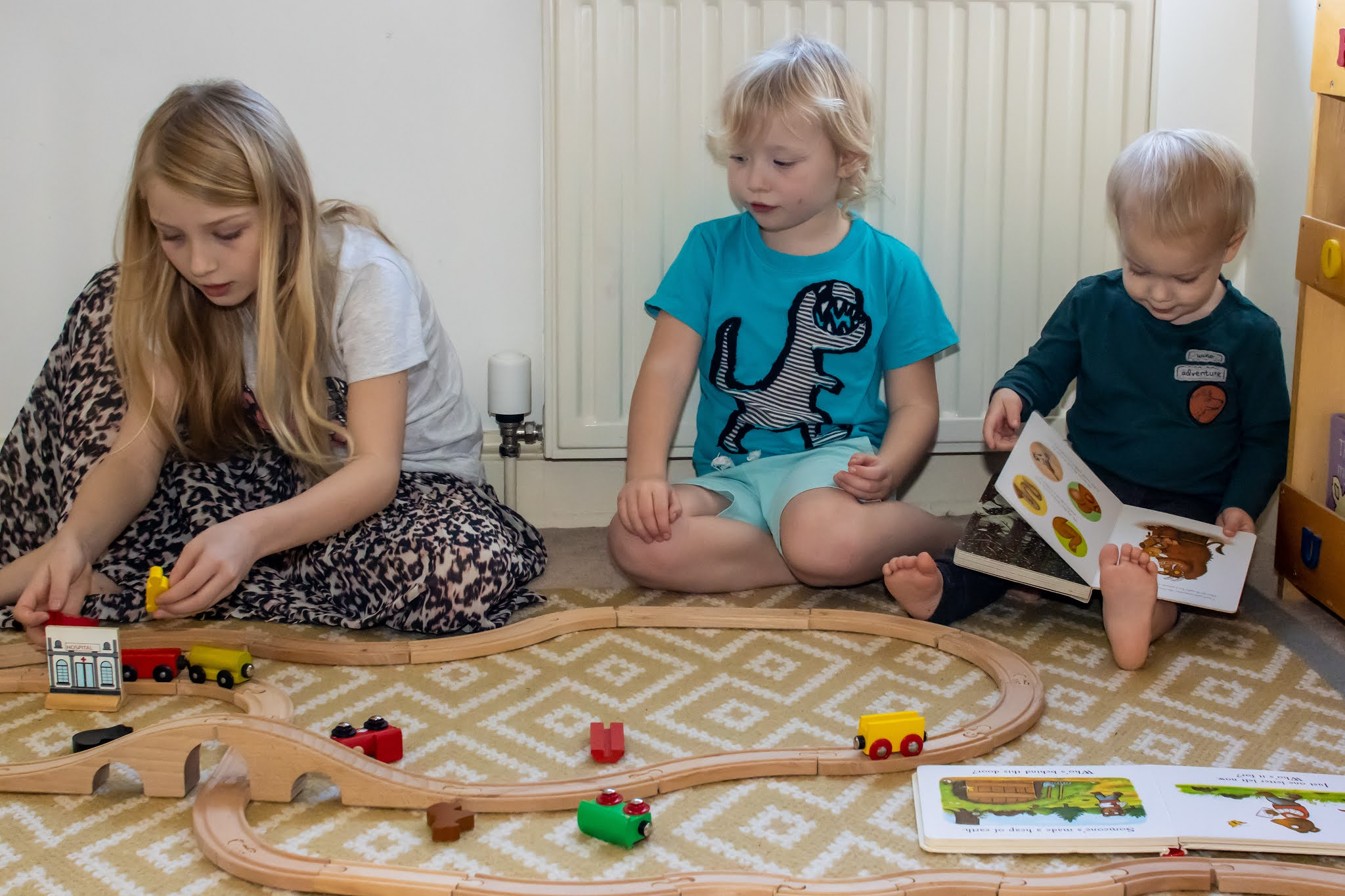 3 children playing in front of a radiator with a hive heating thermostat valve, 2 are playing with a wooden train track and one is reading a book