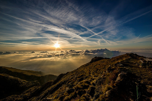 sun rising over a beautiful scenic mountain landscape above the clouds