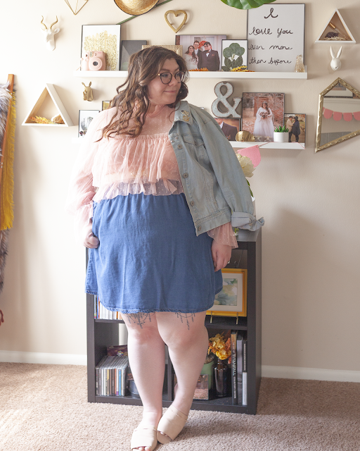 An outfit consisting of a light blue denim jacket, a pastel pink layered sheer blouse layered over a dark blue denim skirt and pink slide sandals.