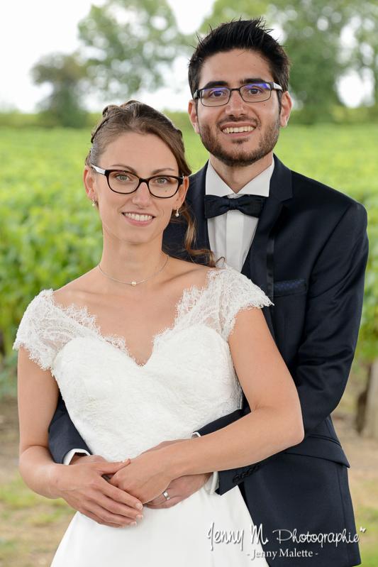 portrait des mariés, la mariée dans les bras du marié, le marié tient la mariée par la taille