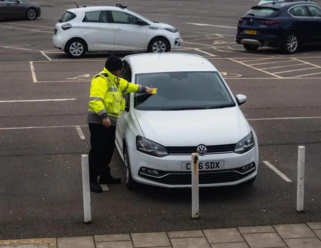 aprende ingles trafico guardia oficial poniendo multa a coche aparcamiento parking