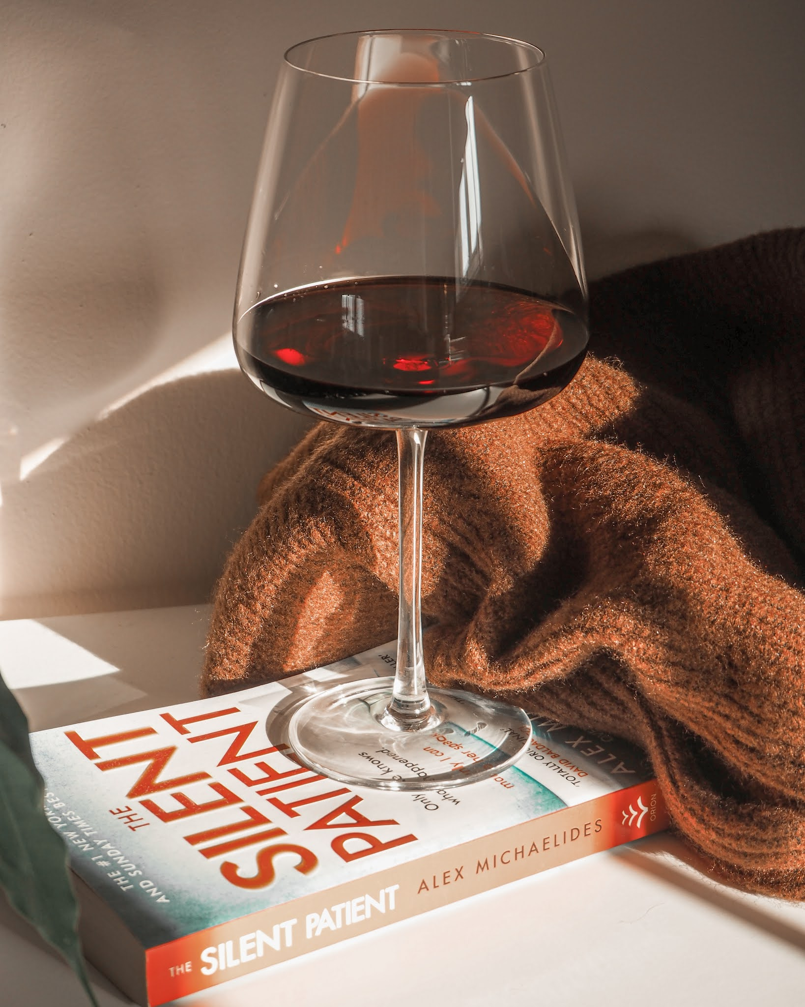 The Silent Patient book and glass of red wine