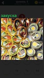 На большом столе в разных мелких тарелочках находится разнообразная закуска
