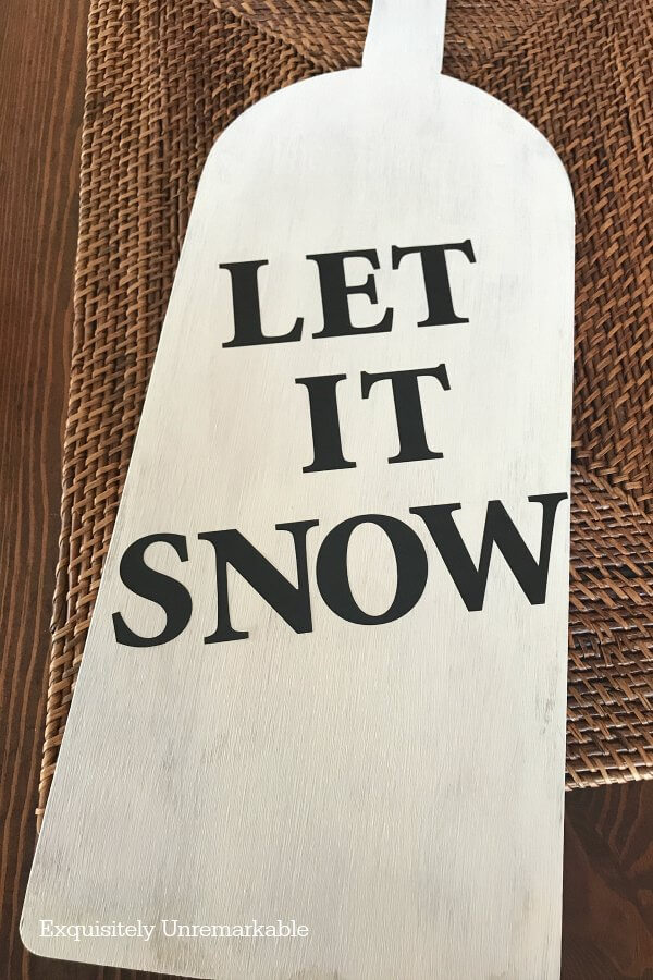 Black Let It Snow Letters on a white painted board