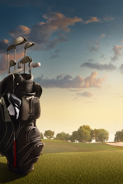 Sunrise on a golf course with a bag full of clubs in the foreground.