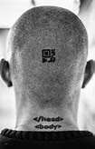 Tattoo of HTML tags on the back of the head of a Columbian hacker that rigged many elections