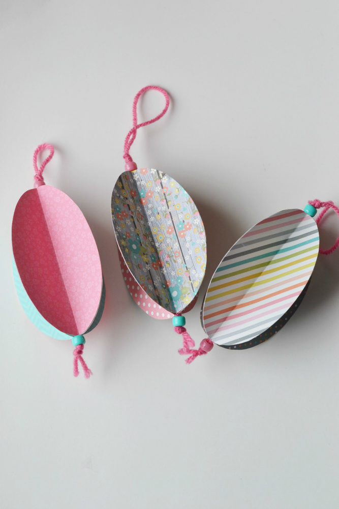 Beautiful Easter ornaments made from decorated cardstock hanging from pink string with aquamarine and pink beads.