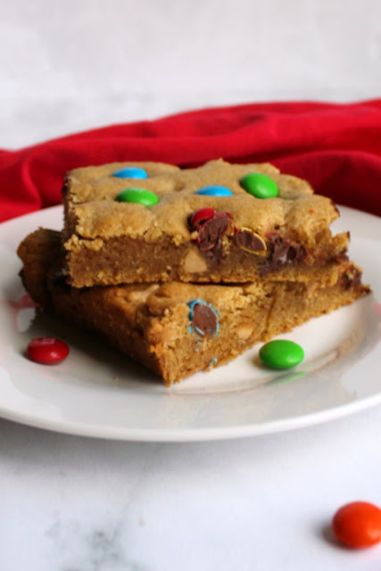 two pieces of chewy salted caramel m&m blondies stacked on plate with soft centers showing