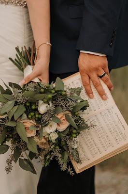 Novios, él con una partitura y ella con un ramo con rosas